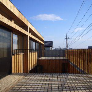 間伐材の丸太で囲まれた2世帯の家